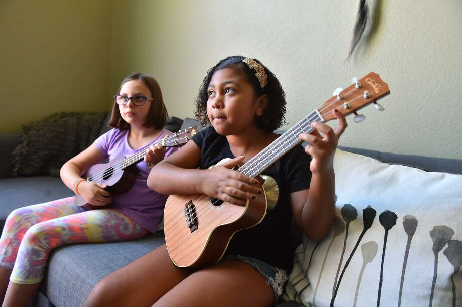 Adalynn Cuevas (right) and Ella Mathias practice the ukulele during their weekly lesson. They are not the lone ukulele rockers of a generation. The instrument's rising popularity among school kids like Cuevas and Mathias is a part of a wider revival story that has spanned almost four decades. Photo: Robin Jerstad / Contributor / ROBERT JERSTAD