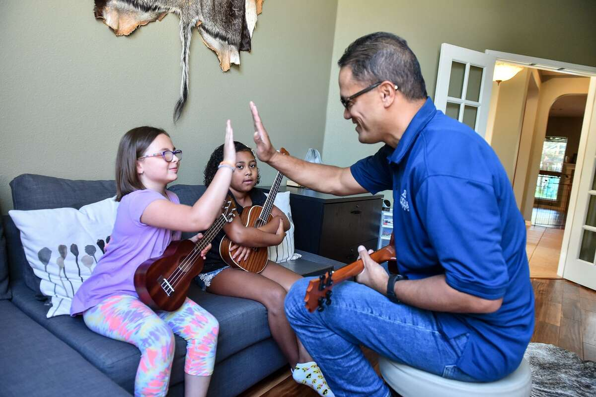 """Kamaka rewards his students with a high-five after they play a chord pattern or attempt a new song. During this lesson in late July, the girls began to learn """"When the Saints Go Marching In."""""""