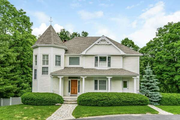 The clapboard colonial house at 860 Silvermine Road has Victorian elements including a two-story turret and scalloping and gingerbread detailing on the front façade.