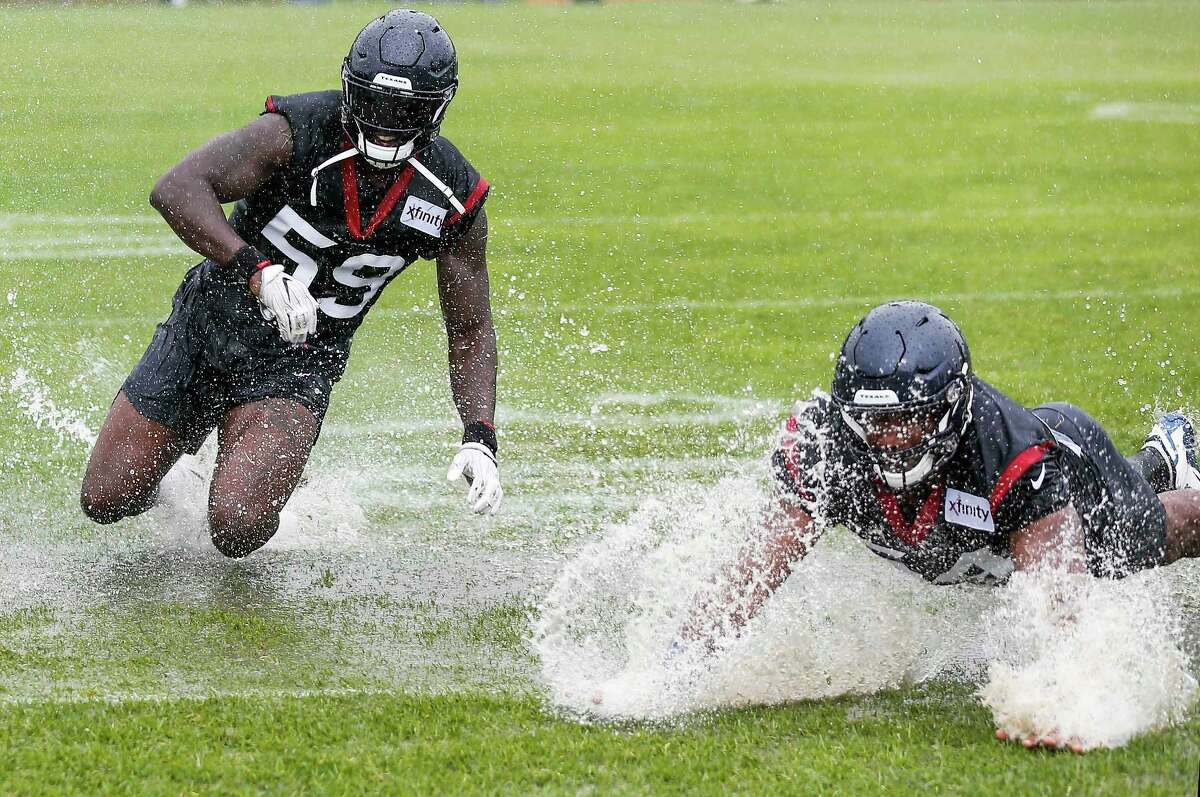 Houston Texans linebackers Whitney Mercilus (59) and LaTroy Lewis slide in a puddle of water on the practice field at the end of practice during training camp at the Greenbrier Sports Performance Center on Friday, Aug. 3, 2018, in White Sulphur Springs, W.Va. A steady rain fell throughout practice.
