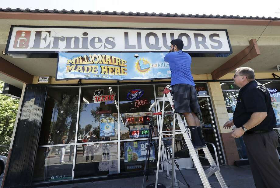 California Lottery official Mike Neis, right, watches as Amol Sachdev hangs a sign over his family's store Ernie's Liquors in San Jose, on July 25. Lottery officials said an office pool of 11 people bought the winning ticket here. (AP Photo/Jeff Chiu) Photo: Jeff Chiu / Associated Press