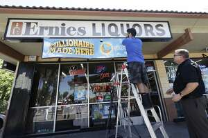 California Lottery�official Mike Neis, right, watches as Amol Sachdev hangs a sign over his family's store Ernie's Liquors in San Jose, Calif., Wednesday, July 25, 2018. The California Lottery says one lucky person won the Mega Millions lottery. The state lottery's verified Twitter feed says the winning ticket, worth more than $500 million, was sold at Ernie's Liquors. (AP Photo/Jeff Chiu)