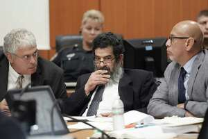 In this June 25, 2018 photo,  Ali Mahwood-Awad Irsan, center, sits in court with his defense attorneys Allen Tanner, left, and Rudy Duarte, right, in Houston. Irsan, a 60-year-old Jordanian-American, is charged with capital murder, accused of killing his daughter's husband and her best friend, an Iranian activist.  (Melissa Phillip/Houston Chronicle via AP)