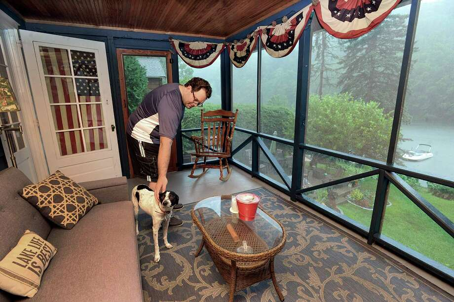 Rob White watches a rain storm with his dog, Lucy, from the screened in porch of his Candlewood Lake home in New Fairfield Thursday, August 2, 2018. Rob and his wife, Kate, have been renting out their home on Candlewood Lake on Airbnb for three years. Photo: Carol Kaliff, Hearst Connecticut Media / The News-Times