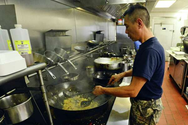 Wai Ming Au-Yeung, owner of China Xpress, prepares a customers order in the kitchen of the restaurant in Stamford, Connecticut on August 3, 2018. Police and the city's health department are investigating claims of a fried mouse was found in an order of fried rice.