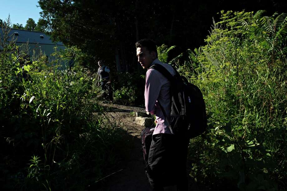 Omer Malik, 19, takes a last look back toward the United States before crossing illegally into Canada at the end of Roxham Road in Champlain, N.Y., on July 18. Photo: Photo For The Washington Post By Andre Malerba / Andre Malerba