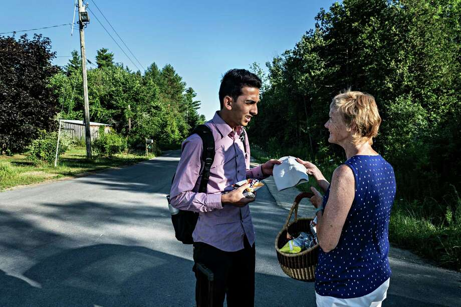 Omer Malik accepts a hat from Janet McFetridge, one of the most visible refugee advocates, before continuing to the end of Roxham Road and illegally crossing into Canada. Malik came to the United States from Ghazni, Afghanistan. Photo: Photo For The Washington Post By Andre Malerba / Andre Malerba