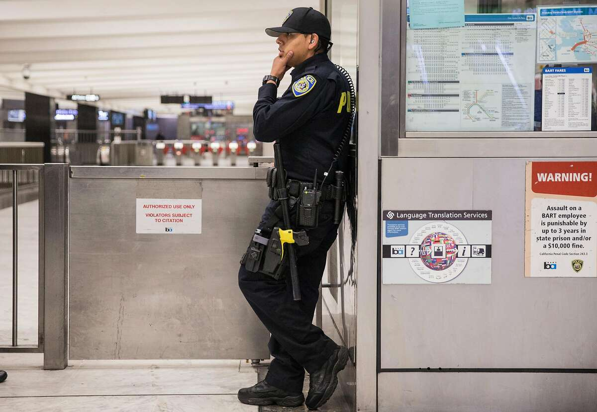 A Bart police officer patrols the side gate on the main floor of the Civic Center Bart Station in San Francisco.