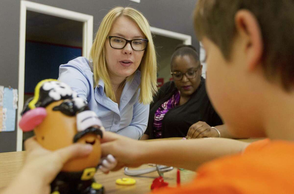 Liz Fajaredo, a board certified assistant behavior analyst, helps a student with a toy as they work on social skills during class at the Texas Autism Academy, Tuesday, Sept. 26, 2017, in Spring.