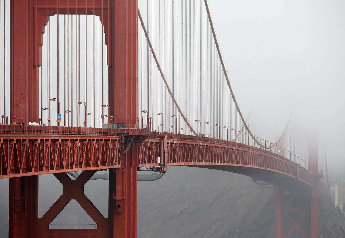 The towers of the Golden Gate Bridge disappear into the fog in San Francisco, Calif. on Friday, Aug. 3, 2018. Construction on a new suicide deterrent barrier below the bridge's deck will begin soon.