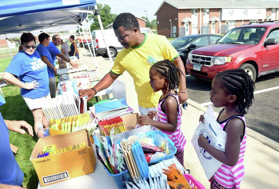Left to right, Reuben Walters picks out school supplies with his twin daughters, Reunell and Reunick, 5, at Meadow Landing Apartments in West Haven during the 2015 Westies on Wheels event in this file photo. This year's Westies on Wheels, in which busloads of schools supplies and information will be distributed at four locations in West Haven, takes place on Thursday, Aug. 9, 2018. The four locations are Meadow Landing, the WH Housing Authority office at 15 Glade St., Forest School and the Savin Rock Conference Center. Photo: Arnold Gold / Hearst Connecticut Media File Photo