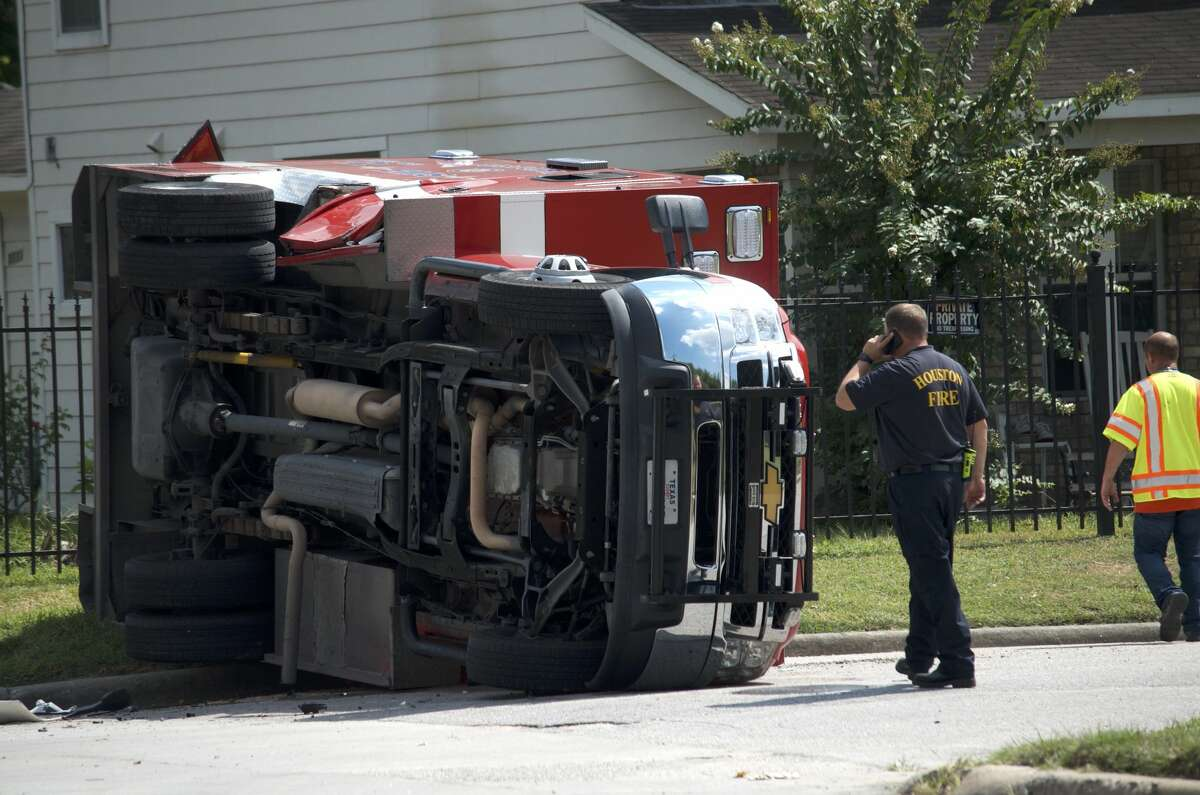 A Houston firefighter observes damage after a Houston Fire Department ambulance flipped over in a crash Friday, Aug. 3, 2018.