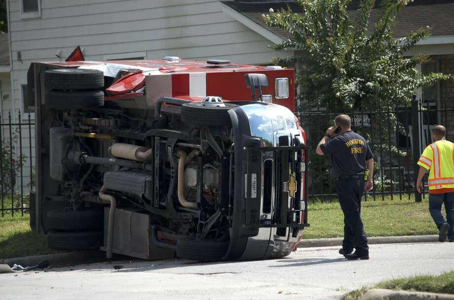 A Houston firefighter observes damage after a Houston Fire Department ambulance flipped over in a crash Friday, Aug. 3, 2018. Photo: Jay R. Jordan