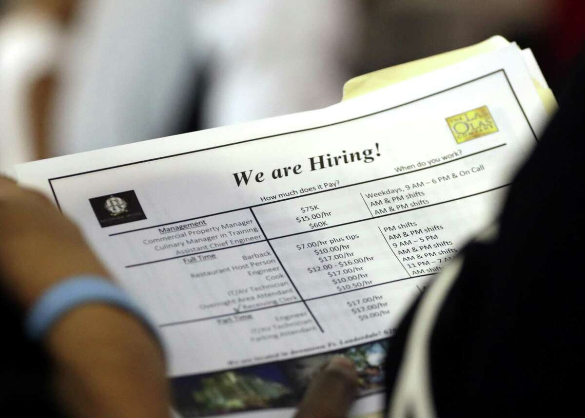 In this June 21, 2018 file photo, a job applicant looks at job listings for the Riverside Hotel at a job fair hosted by Job News South Florida, in Sunrise, Fla.