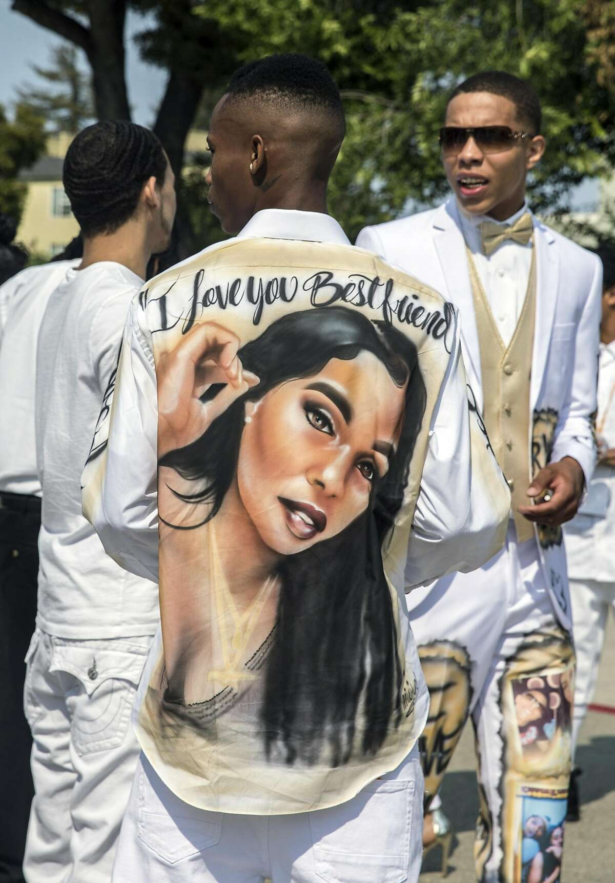 Duce, center, friend of Nia Wilson sports a custom-made suit during a funeral service held for 18-year-old Nia Wilson of Oakland at Acts Full Gospel Church in Oakland, Calif. Friday, Aug. 3, 2018. Wilson was killed Sunday, July 22, 2018 at Macarthur Bart station in Oakland, Calif.