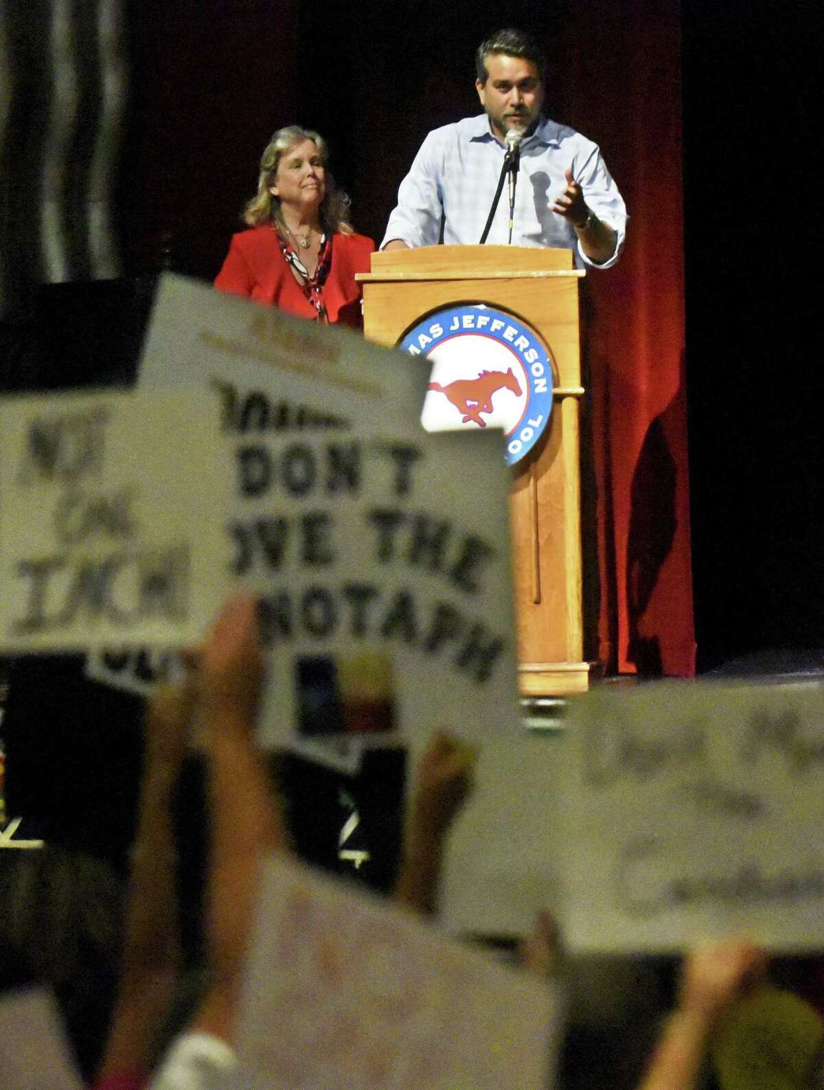 Councilman Robert Trevino and City of San Antonio Archaeologist Kay Hindes listen as people opposed to moving the Cenotaph express themselves during a July 18 meeting at Jefferson High School.