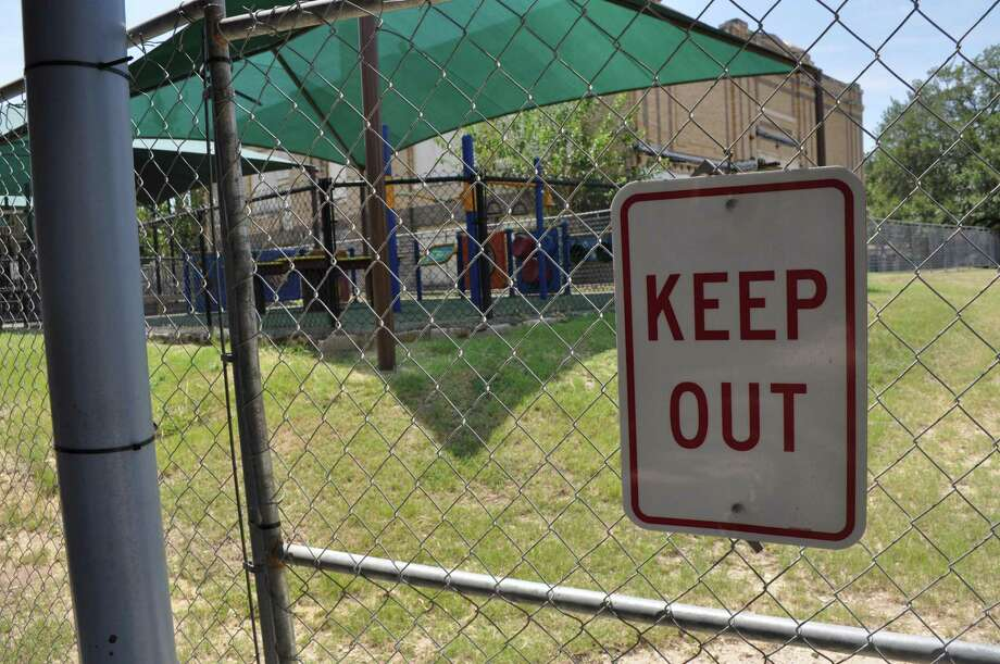 Children are fenced off from a playground at Beacon Hill Academy because the building is considered unsafe. Parents want a solution. Photo: Josh Brodesky /Express-News