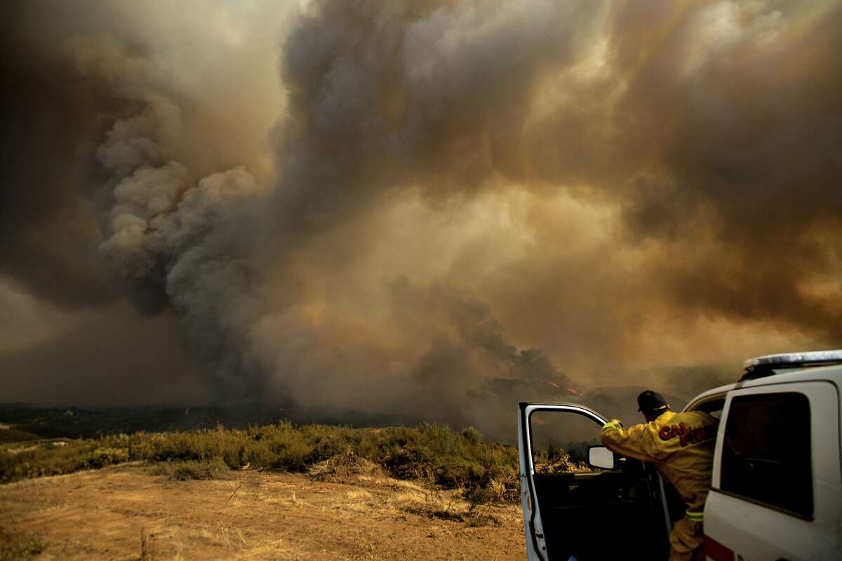 Cal Fire Division Chief Mark Higgins directs helicopters dropping water as the River Fire burns in Lakeport, Calif., Tuesday, July 31, 2018. (AP Photo/Noah Berger)