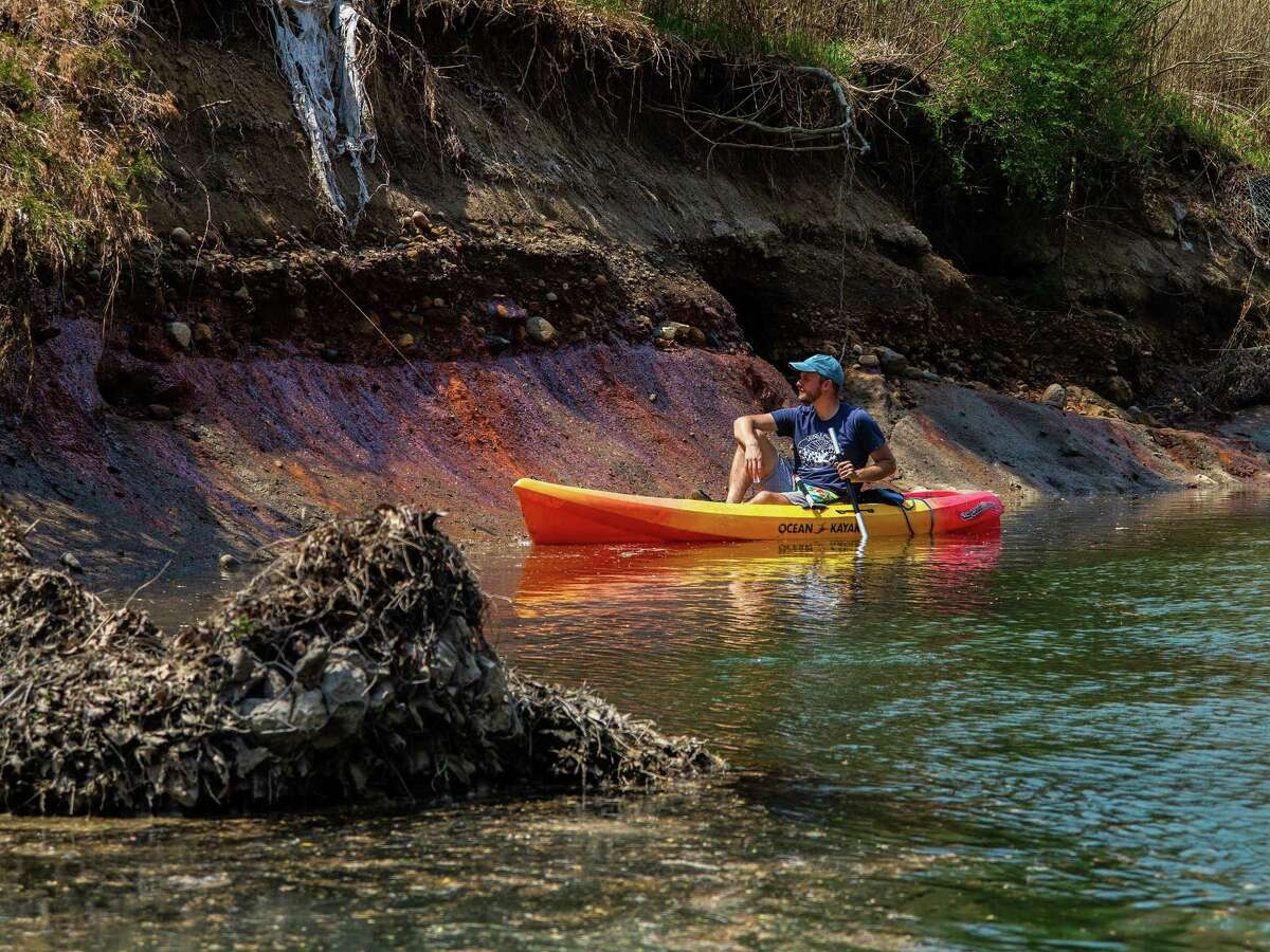Andrew Rehn of Prairie Rivers Network from Champaign, Ill., looks at toxic coal ash waste seepage on the shore of the Middle Fork of the Vermilion River, near Collison on May 2 in Illinois. Wanting to preserve the planet is a goal of progressives.