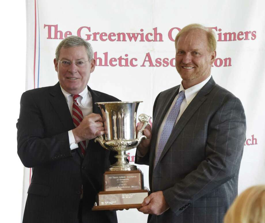 Greenwich High School rugby coach Joe Kelly, right, accepts the Greenwich Old Timers Athletic Association lifetime achievement award from Association President John Rogan at Greenwich Country Club in Greenwich, Conn. Tuesday, June 12, 2018. Kelly has been a lifetime rugger and the GHS team has seen tremendous success, including six straight trips to he National Championship, under his leadership the last eight years. Photo: Tyler Sizemore / Hearst Connecticut Media / Greenwich Time