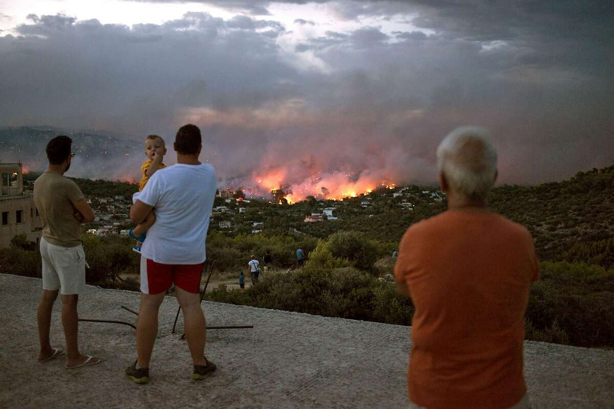 """TOPSHOT - EDITORS NOTE: Graphic content / People watch a wildfire in the town of Rafina, near Athens, on July 23, 2018. At least 20 people have died and more have been injured as wild fires tore through woodland and villages around Athens on Monday, while blazes caused widespread damage in Sweden and other northern European nations. More than 300 firefighters, five aircraft and two helicopters have been mobilised to tackle the """"extremely difficult"""" situation due to strong gusts of wind, Athens fire chief Achille Tzouvaras said. / AFP PHOTO / ANGELOS TZORTZINISANGELOS TZORTZINIS/AFP/Getty Images"""
