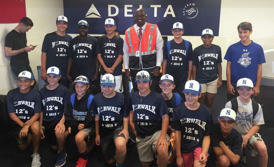 Members of the Norwalk 12-year-old Cal Ripken All-Stars pose for a photo with Delta supervisor Marcus Benjamin near the end of a 10-hour flight delay while en route to Branson, Mo., for the Cal Ripken World Series. Benjamin helped the team charter a flight by finding flight crew members to get the team to Missouri in time for Friday's opening ceremonies. Photo: Contributed Photo