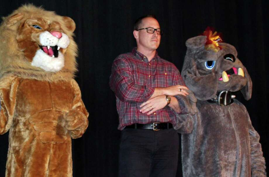 Woodcreek Middle School principal Bryan Applegate, who has been called to active duty service, stands onstage at Summer Creek High School next to Woodcreek's lion mascot and Summer Creek's bulldog mascot during a teacher talent show in May. Photo: Melanie Feuk / Melanie Feuk