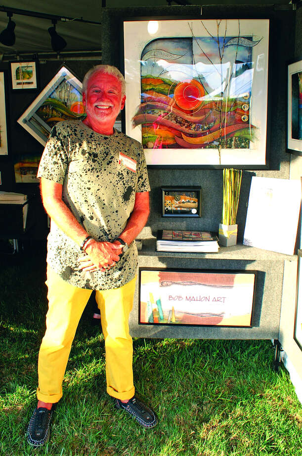 A dealer stands with some of his art pieces. Photo: For The Intelligencer