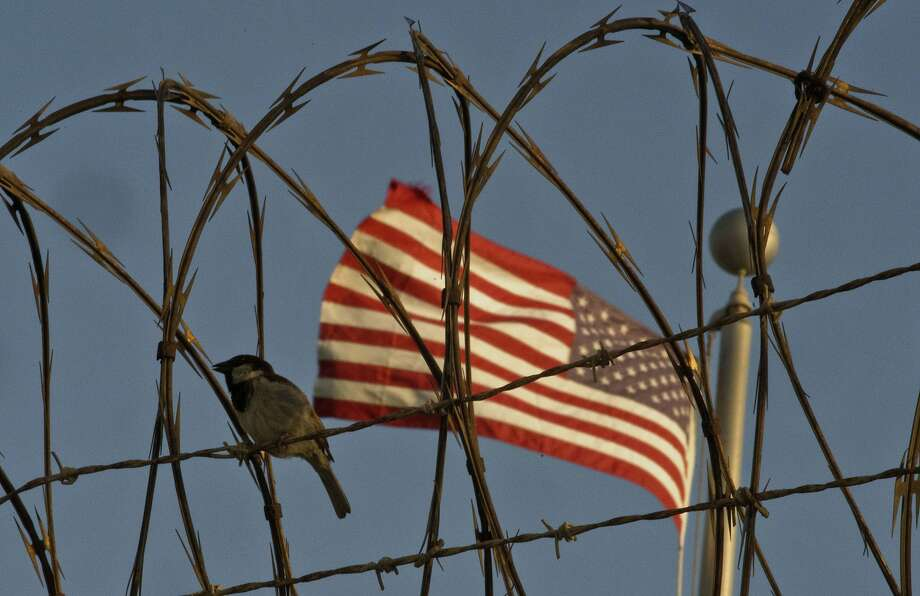 In this June 5, 2018 photo reviewed by U.S. military officials, a bird perches on barbed wire where a U.S. flag flies at the Camp VI detention facility on the Guantanamo Bay U.S. naval base in Cuba. The two Guantanamos have been a contrast since the U.S. opened the base at the southeastern tip of the island in 1903, following the Spanish-American War, and the divide has only grown under Cuba's communist government, which refuses to cash the annual rent checks from Washington as it insists the U.S. leave. (AP Photo/Ramon Espinosa) Photo: Ramon Espinosa, Associated Press