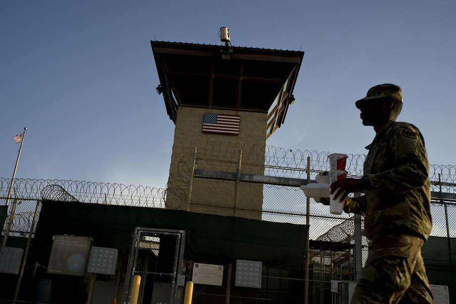 A U.S. soldier carries food past the detention facility at the Guantanamo Bay naval base in Cuba. Five defendants are on trial there for the Sept. 11 attacks. Photo: Ramon Espinosa / Associated Press 2018