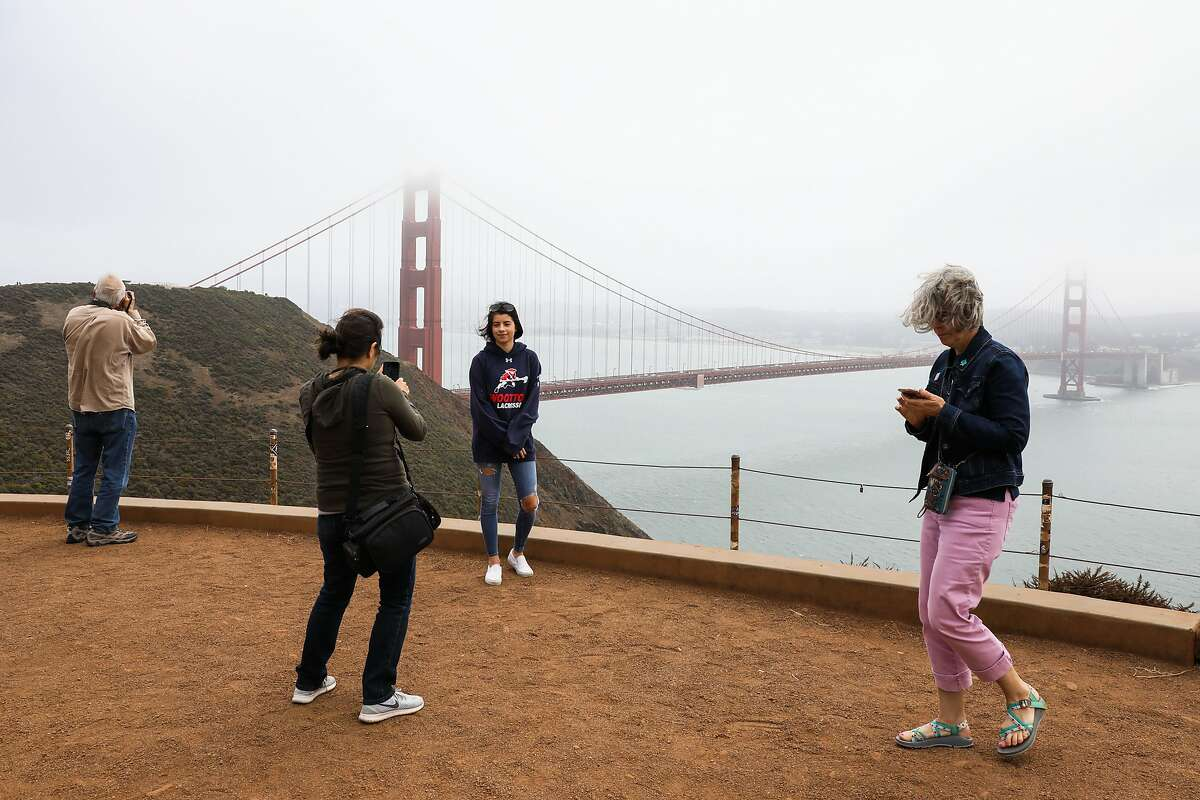 Lubima Petrova (center,left) takes a photograph of her daughter Rumi Petrova (center,right) at the Golden Gate Bridge in the fog in Sausalito, California, on Thursday, August 2, 2018.