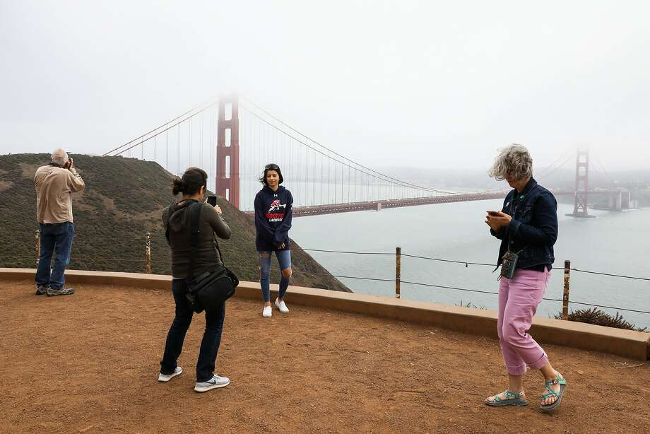 File -- Lubima Petrova (center,left) takes a photograph of her daughter Rumi Petrova (center,right) at the Golden Gate Bridge in the fog in Sausalito, California, on Thursday, August 2, 2018. Photo: Gabrielle Lurie / The Chronicle