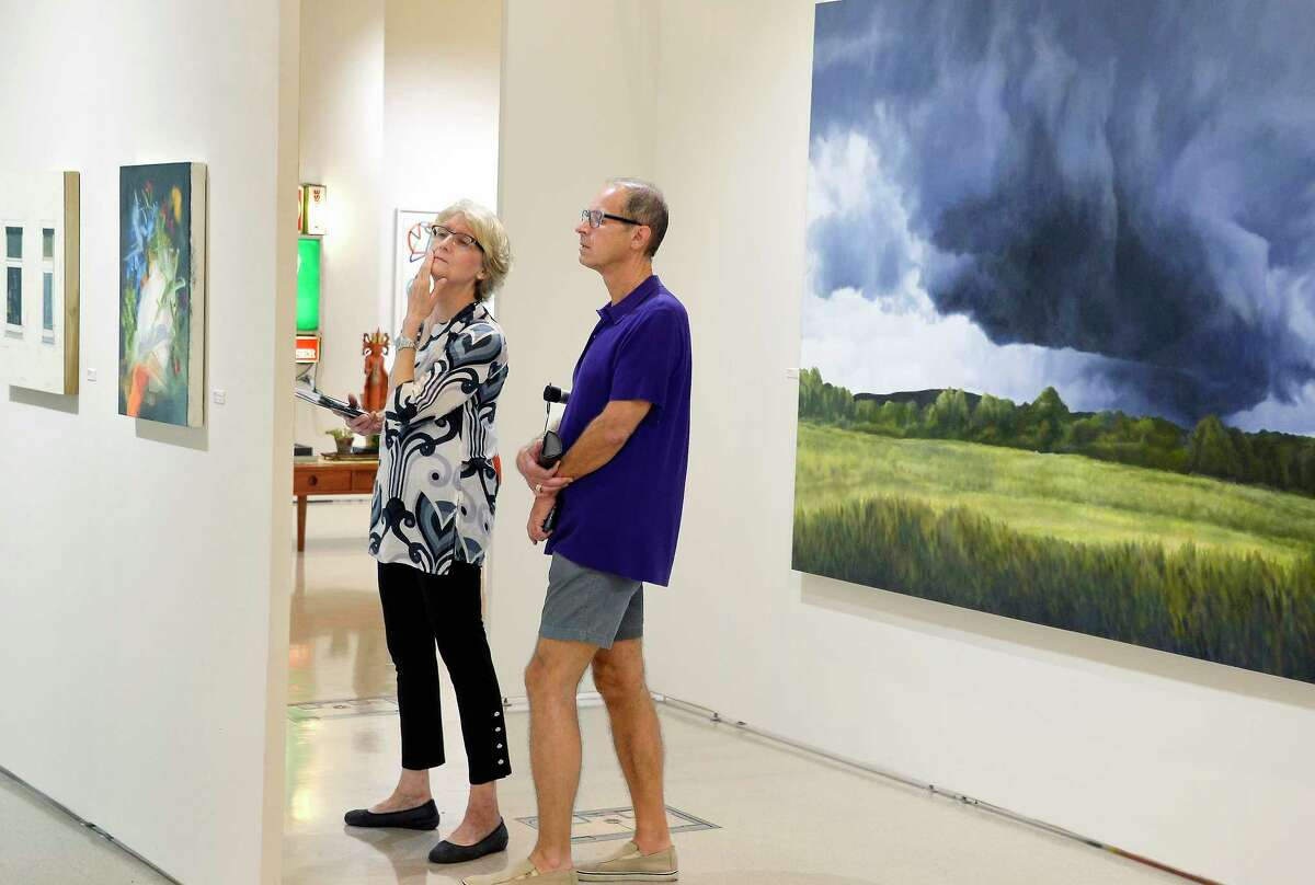 Catherine Minnery of Ballston Spa and Ken Klemp of Loudonville take in the REVEAL International Contemporary Art Fair at the Center Center Friday August 3, 2018 in Saratoga Springs, NY. (John Carl D'Annibale/Times Union)