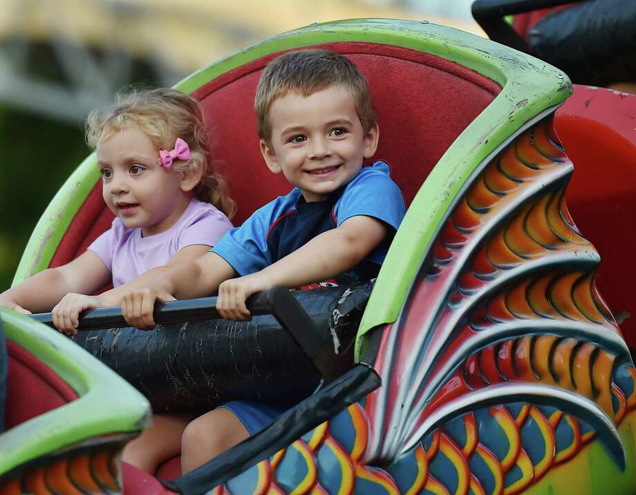 Carter Tonucci, 4, and his 2-year-old sister Emma, of Orange ride the Orient Express at the annual Orange Volunteer Firemen's Carnival at 525 Orange Center Road at the Orange Fairgrounds Friday, August 3, 2018. The carnival runs  August 4 from noon to midnight, and August noon - 5 p.m. Photo: Catherine Avalone, Hearst Connecticut Media / New Haven Register
