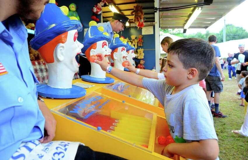 Luca Fracassini, 5, of Fairfield, plays a game of chance during Easton's 77th Annual Fireman's Carnival in Easton, Conn., on Friday Aug. 3, 2018.