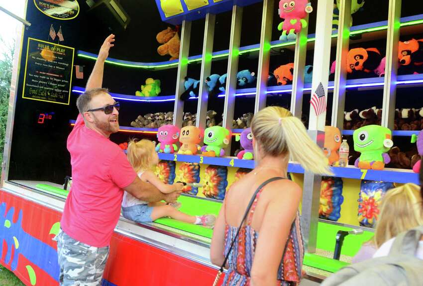 Kyle Miller, of Fairfield, yells out after he and his daughter Quinn, 2, win a game of chance during Easton's 77th Annual Fireman's Carnival in Easton, Conn., on Friday Aug. 3, 2018.