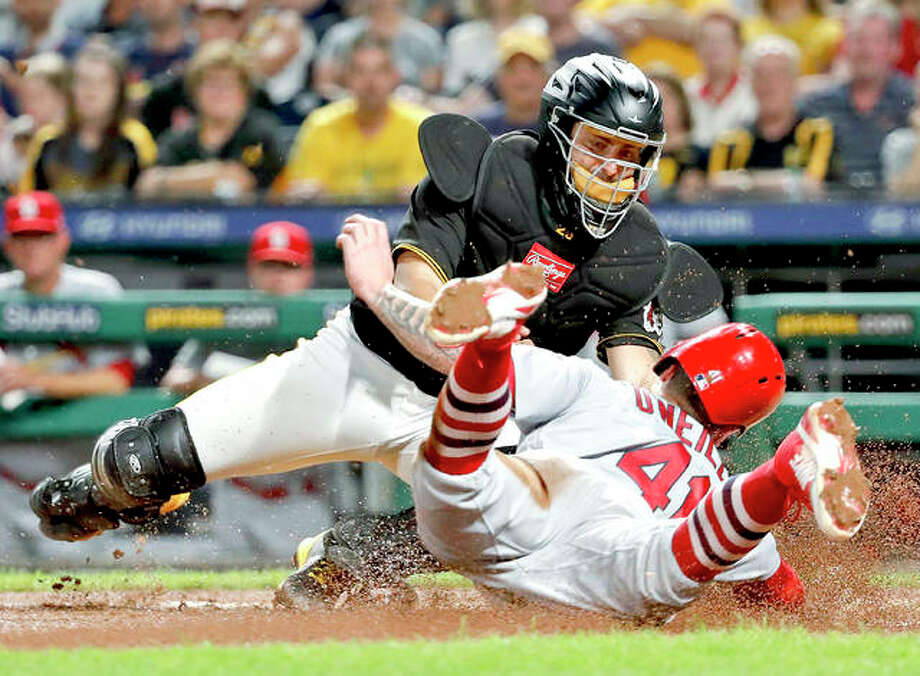 Pirates catcher Francisco Cervelli, top, tags out the Cardinals' Tyler O'Neill during the eighth inning of Friday night's game in Pittsburgh. Photo:     AP