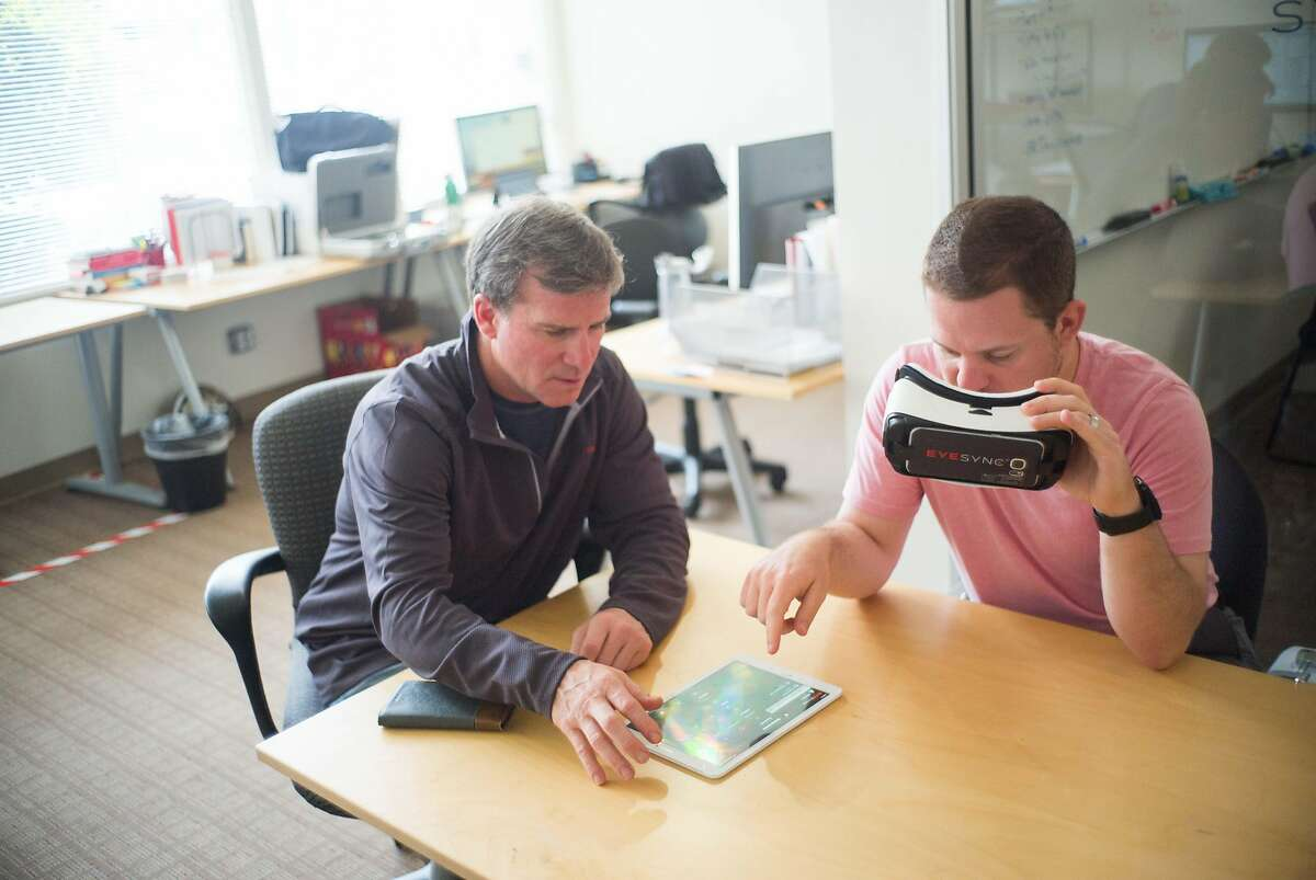 Doug Appleton, left, and Matt Mills demonstrate their headset's eye tracking capabilities at SyncThink in Palo Alto, Calif. on Friday, Aug. 3, 2018. The headset uses eye tracking to detect if users might be concussed.