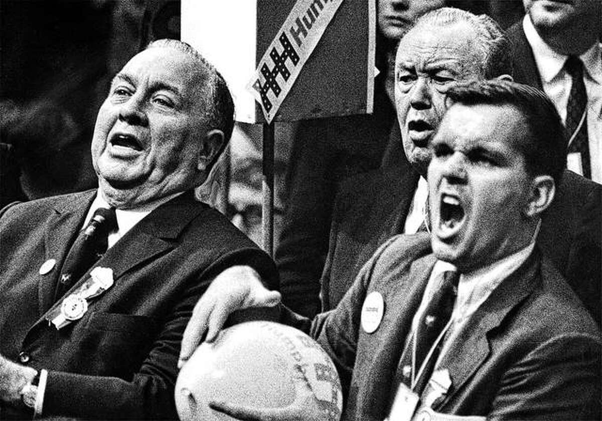 Mayor Richard J. Daley and son Richard M. Daley jeer Sen. Abraham Ribicoff at the 1968 Democratic National Convention as he criticizes Chicago police tactics.