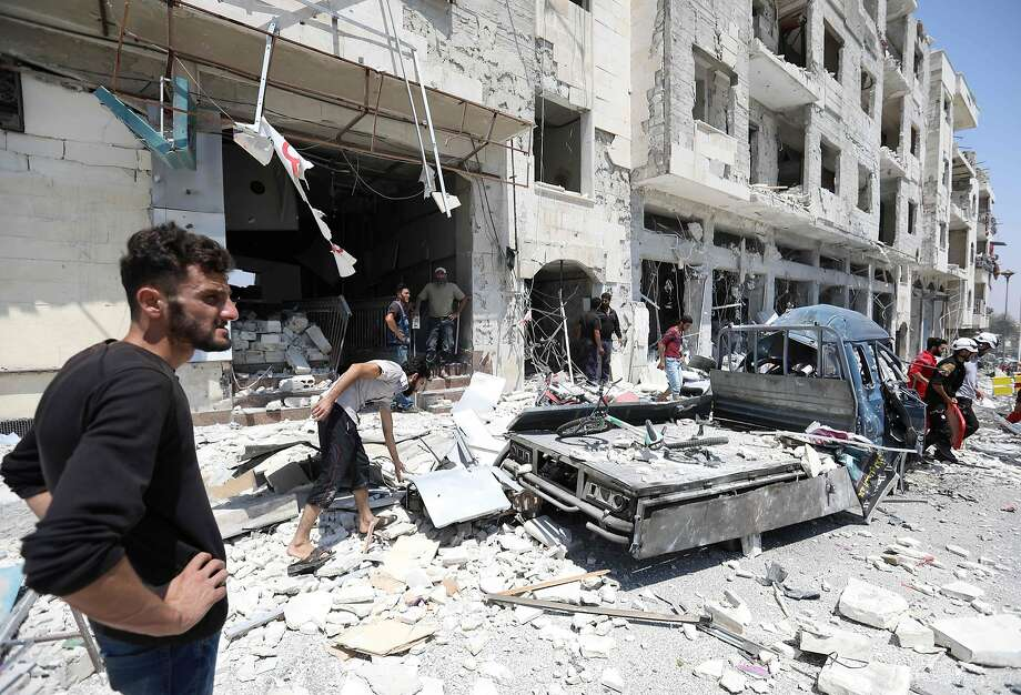 Residents examine the site of car bombing Thursday in the city of Idlib, the capital of a province held by opposition forces. Photo: Omar Haj Kadour / AFP / Getty Images