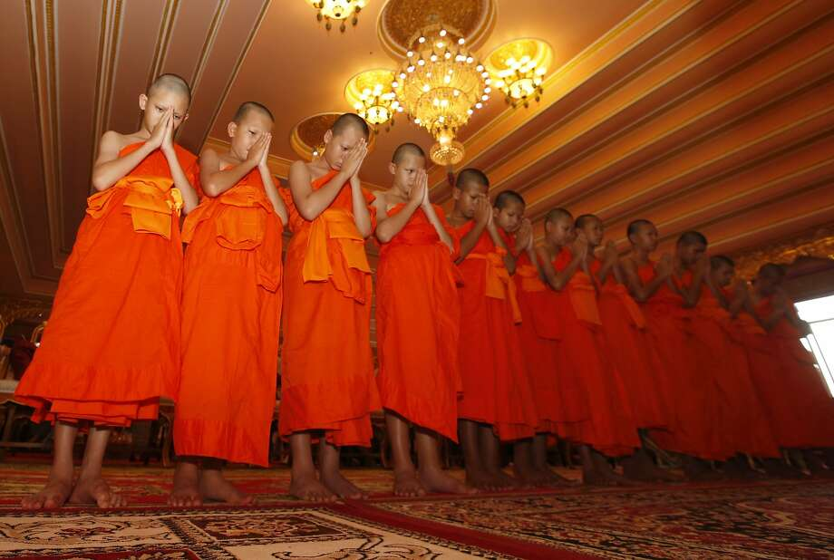 Members of Wild Boars soccer team pray during a ceremony marking the completion of their time as novice Buddhist monks in the Chiang Rai province of northern Thailand. Photo: Sakchai Lalit / Associated Press