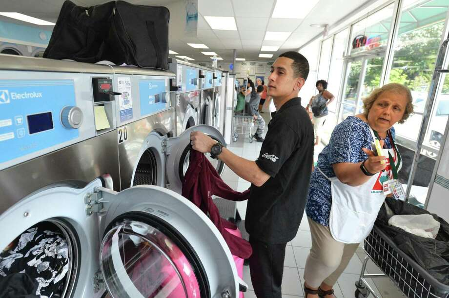 Jeff Chanholm loads a washing machine full of his clothes at Giant Laundry in East Norwalk with help from volunteer Darunee Wilson from St. Lukes Church in Darien with the Laundry Love program. The nonprofit helps people and families in need with averything they may need to do laundry, incuding a donated pizza lunch on Wednesday August 1, 2018 in Norwalk Conn. Photo: Alex Von Kleydorff / Hearst Connecticut Media / Norwalk Hour