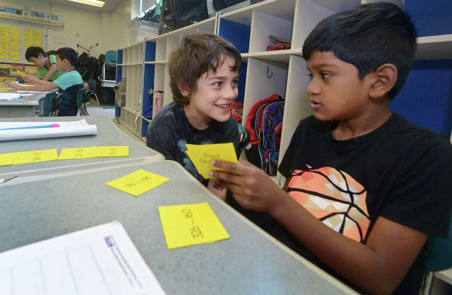 Adrian Adam and Eric Victor, both 7, play a math game as part of the Summer SPARK program Tuesday, July 17, 2018, at Brookside Elementary School in Norwalk, Conn. The SPARK program partners with UCONN to give K-2 kids who might be eligible for the gifted program in 3rd grade more experiences and skills. Photo: Erik Trautmann / Hearst Connecticut Media / Norwalk Hour