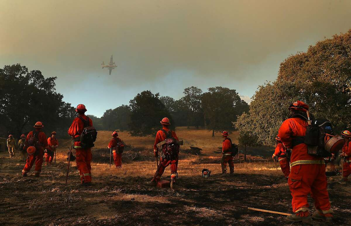 LAKEPORT, CA - AUGUST 01: Inmate firefighters look on as a firefighting aircraft prepares to drop fire retardant ahead of the River Fire as it burns through a canyon on August 1, 2018 in Lakeport, California. The River Fire has burned over 27,000 acres, destroyed 7 homes and stands at 38 percent contained. (Photo by Justin Sullivan/Getty Images)