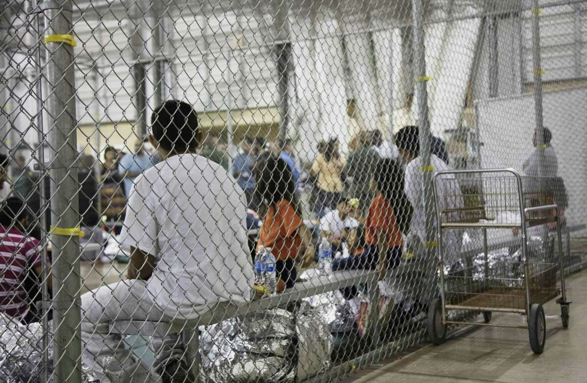 FILE - In this June 17, 2018 file photo provided by U.S. Customs and Border Protection, people who've been taken into custody related to cases of illegal entry into the United States, sit in one of the cages at a facility in McAllen, Texas. Immigrant children described hunger, cold and fear in a voluminous court filing about the facilities where they were held in the days after crossing the border. Advocates fanned out across the southwest to interview more than 200 immigrant parents and children about conditions in U.S. holding facilities, detention centers and a youth shelter. The accounts form part of a case over whether the government is complying with a longstanding settlement over the treatment of immigrant youth in custody. (U.S. Customs and Border Protection's Rio Grande Valley Sector via AP)