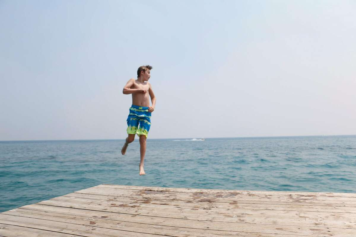 Graham Schlict, 11, of San Antonio jumps off the dock at Sugar Point Beach in South Lake Tahoe. From San Antonio, Schlict visits the area for a week every summer with his parents, who are Bay Area natives. (Photo by Cahner Olson)