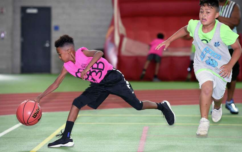 Mahki Henderson, 9, of the Buccaneers Basketball Club goes after a ball heading out of bounds as he is covered by Jonathan Rodriguez, 9, of the Riverside Ballers during the CT Big 3 Ballout at the Floyd Little Athletic Center in New Haven on August 4, 2018. Two hundred and forty athletes on 60 teams from Connecticut, Pennsylvania and New Jersey competed during two days of three on three basketball games.