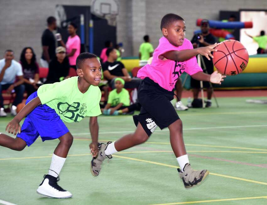 Amari Marion (left), 7, and Logan Davis, 8, of the Buccaneers Basketball Club go after a loose ball during the CT Big 3 Ballout at the Floyd Little Athletic Center in New Haven on August 4, 2018. Two hundred and forty athletes on 60 teams from Connecticut, Pennsylvania and New Jersey competed during two days of three on three basketball games.