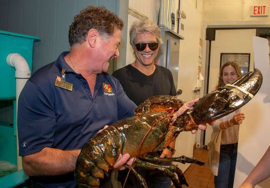Stew Leonard Jr., left, presents Jon Bon Jovi with a 20-pound lobster. Rocker Jon Bon Jovi made a surprise visit to a Stew Leonard's supermarket recently to support a family business venture and to collect some special groceries. Photo: Courtesy Of Stew Leonard's