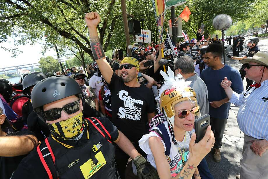 PORTLAND, OR - AUGUST 04: Rally organizer Joey Gibson (center) and right-wing demonstrators hold a rally supporting gun rights and free speech on August 4, 2018 in Portland, Oregon. The rally was organized by the group Patriot Prayer, also attended by the affiliated group Proud Boys, which drew counter protesters and members of the anti-fascist group Antifa.  (Photo by Karen Ducey/Getty Images) Photo: Karen Ducey, Getty Images